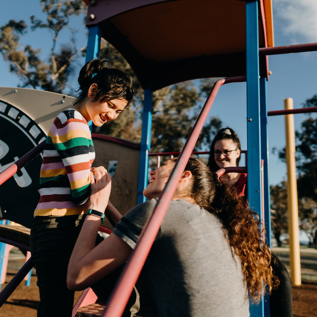 image of young girl on play equipment with carers