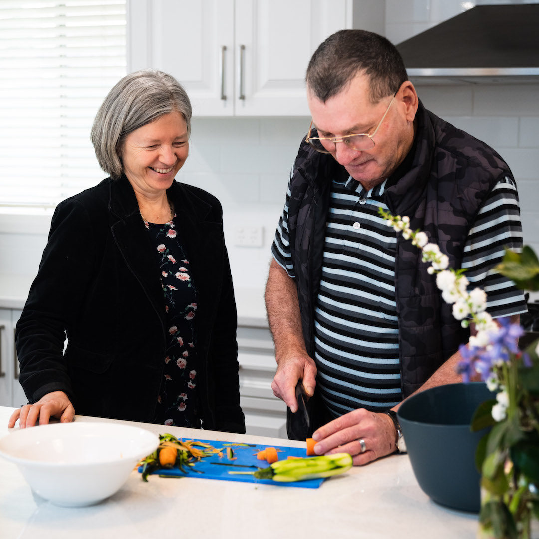 woman watching man to cut vegetables in kitchen